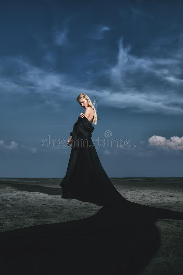 Elegant beautiful woman. Full length portrait of a beautiful gothic woman in long black dress posing outdoor. Beauty, fashion stock photos