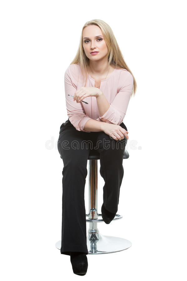 Elegant beautiful woman sitting on a contemporary royalty free stock image
