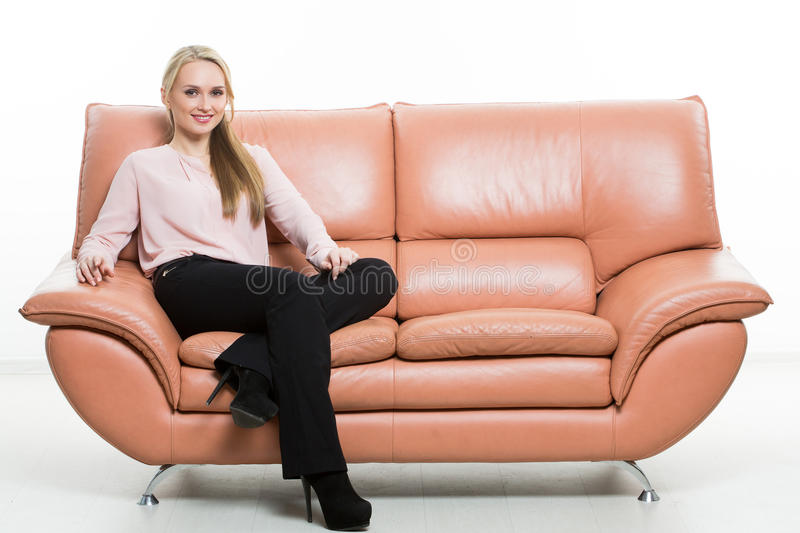 Elegant beautiful woman sitting on a couch a royalty free stock image