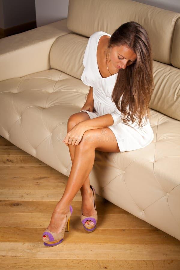 Elegant Beauty On Sofa. Elegantly Beautiful Woman sitting on sofa with long legs royalty free stock photo