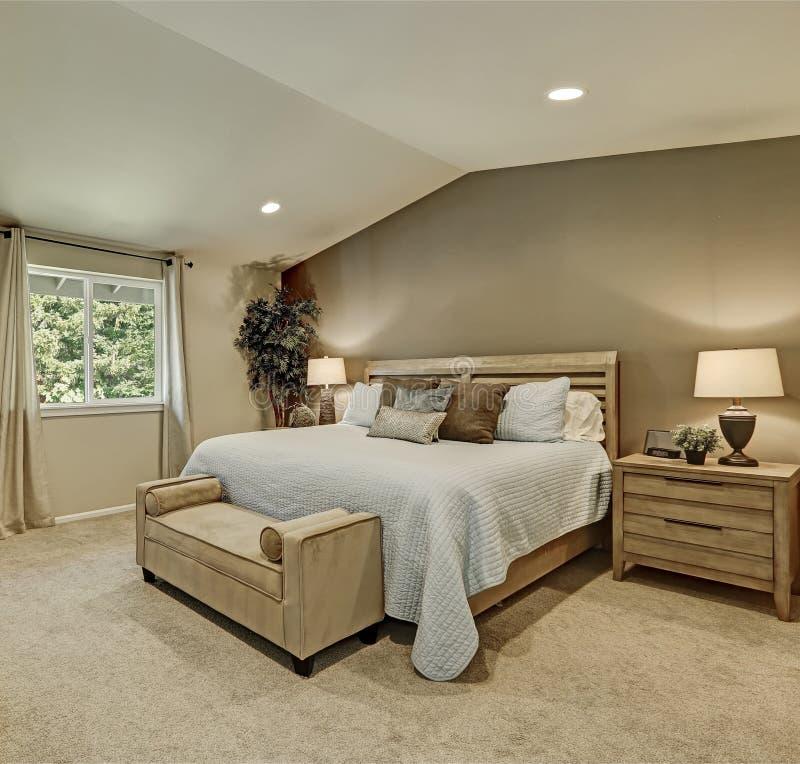 Elegant beige en bruin slaapkamerbinnenland met lichtblauw beddegoed stock foto's