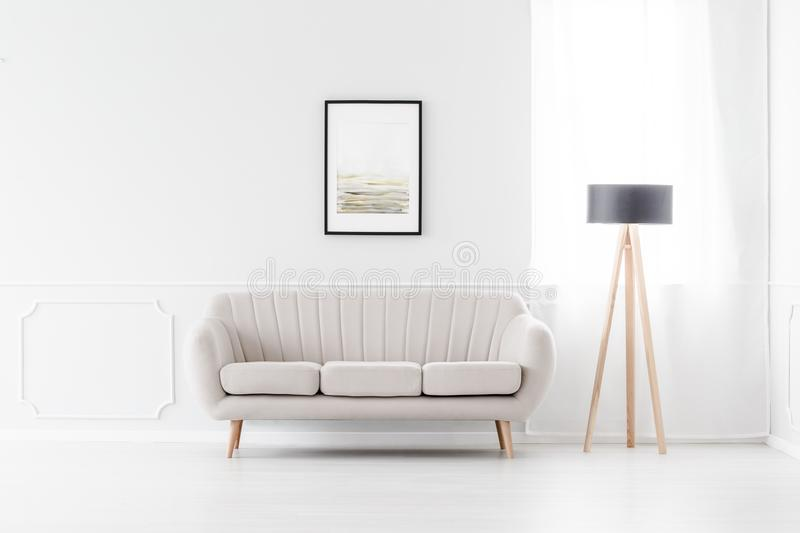 Sofa in empty white interior. Elegant, beige sofa in an empty white interior with art above the sofa and a wooden tripod lamp by a window stock photography