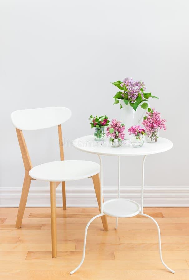 Elegant binnenland met lijst, stoel en de lentebloemen royalty-vrije stock afbeeldingen