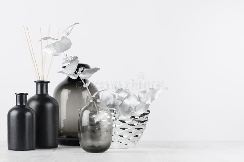 Elegant blank black bottles, glass vase for home decor on soft light white wood table with silver leaves as template. Elegant blank black bottles, glass vase stock image