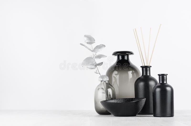 Elegant blank black bottles, glass vase for home decor on soft light white wood table with silver leaves as template. Elegant blank black bottles, glass vase stock photos