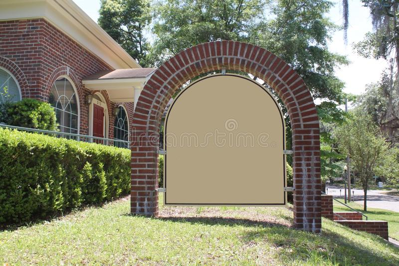 Elegant Blank Sign In Front of Business. Elegant blank sign in front of a brick home renovated to be used a business royalty free stock photos