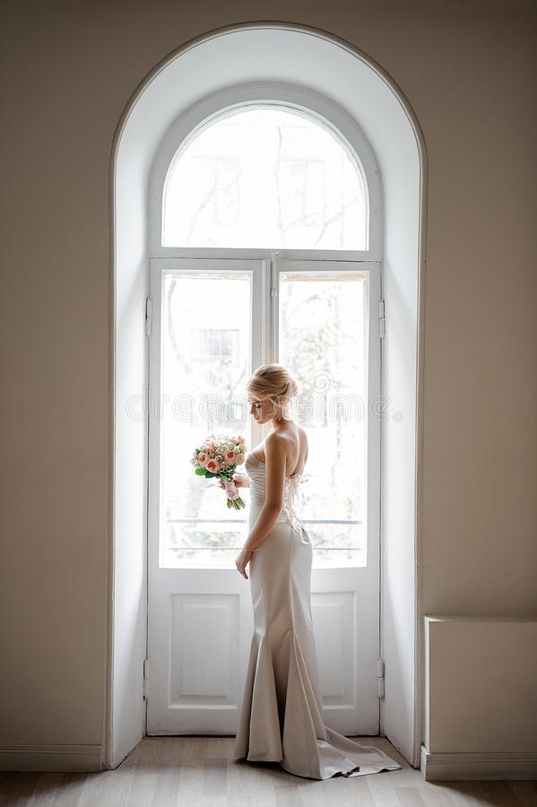 Elegant blond brud i en älskvärd vit klänning som rymmer en bröllopbukett royaltyfri bild