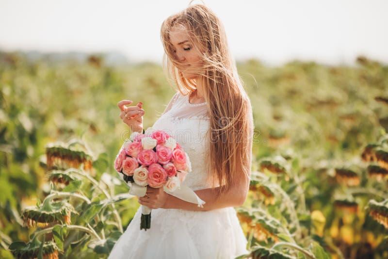 Elegant blond brud med långt hår och en bukett av solrosor i fältet fotografering för bildbyråer