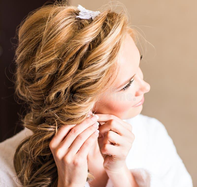 Elegant blond brud som sätter på örhängecloseupen som förbereder sig för att gifta sig royaltyfri bild