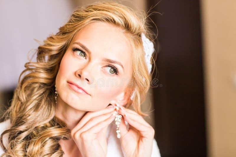 Elegant blond brud som sätter på örhängecloseupen som förbereder sig för att gifta sig royaltyfri fotografi