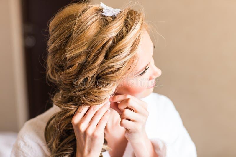Elegant blond brud som sätter på örhängecloseupen som förbereder sig för att gifta sig royaltyfria foton