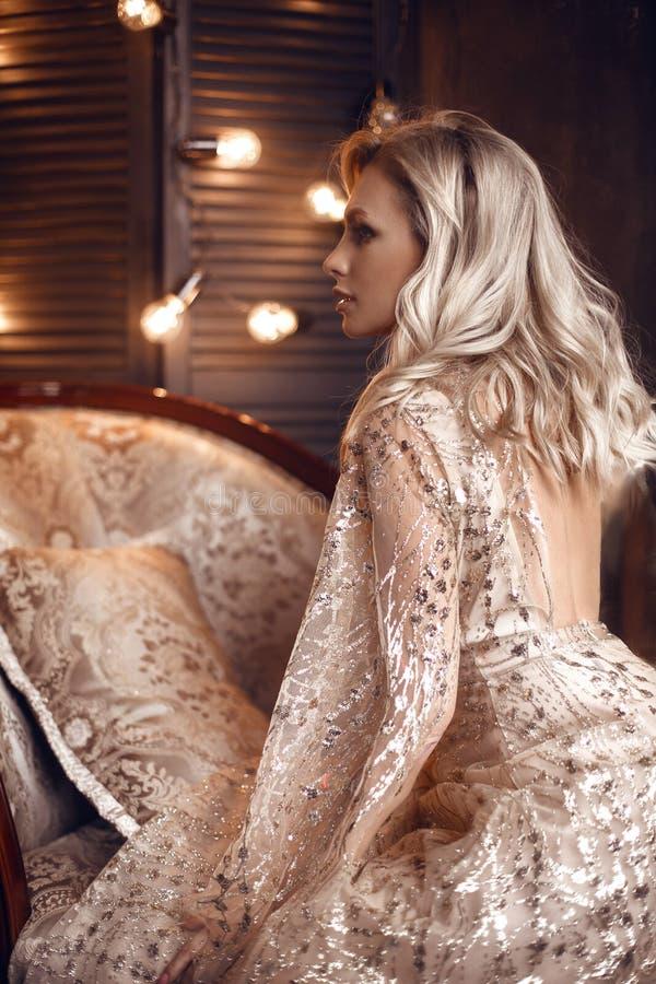 Elegant blond kvinna i den beigea klänningen som poserar på den lyxiga soffan i kunglig inre Härlig sinnlig brud för mode med mak royaltyfri foto