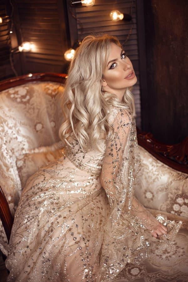 Elegant blond kvinna i den beigea klänningen som poserar på den lyxiga soffan i kunglig inre Härlig sinnlig brud för mode med mak royaltyfria foton