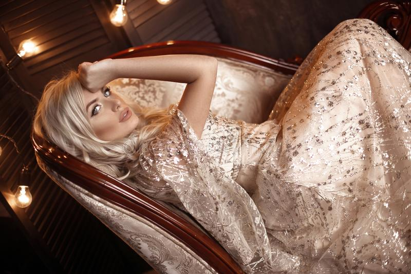 Elegant blond kvinna i den beigea klänningen som poserar på den lyxiga soffan i kunglig inre Härlig sinnlig brud för mode med mak arkivfoto