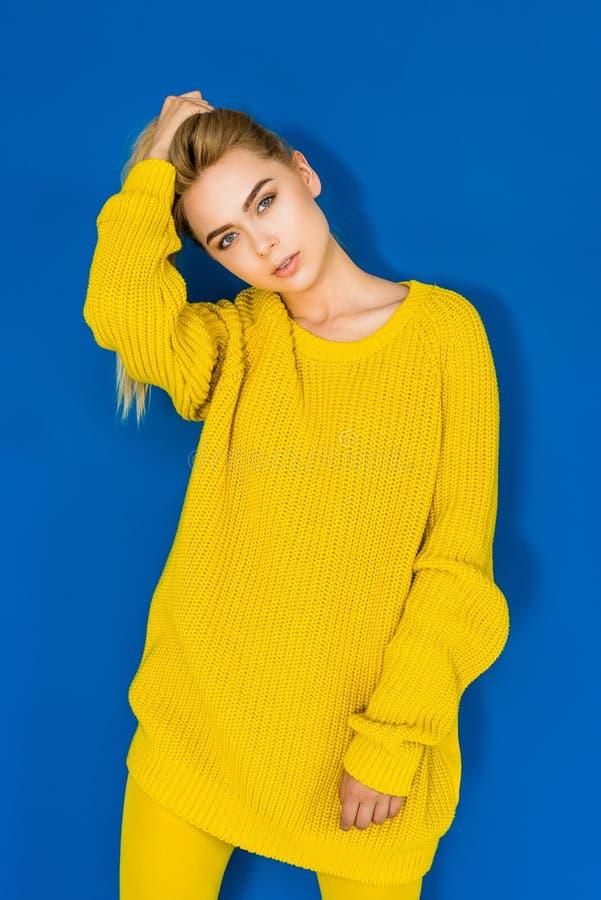 Elegant blond kvinna i gult posera för tröja arkivbilder