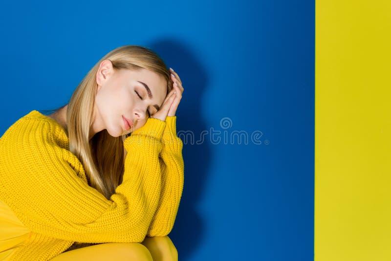 Elegant blond kvinna som drömmer på blått royaltyfri bild