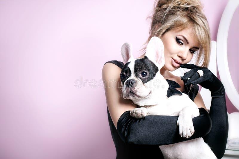 Elegant blond kvinna som poserar med mopshunden arkivfoton