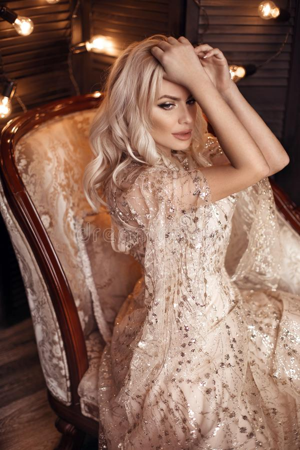 Elegant blond woman in beige dress posing on luxury sofa in royal interior. Fashion beautiful sensual bride with makeup, curly royalty free stock photography