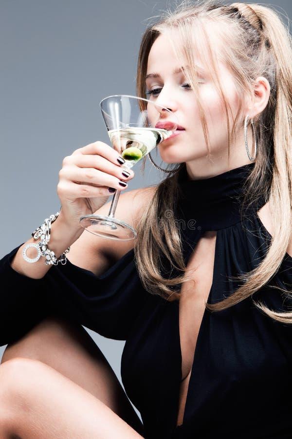 Elegant blond woman drink martini coctail. Blond elegant woman drinking martini, studio shot stock image