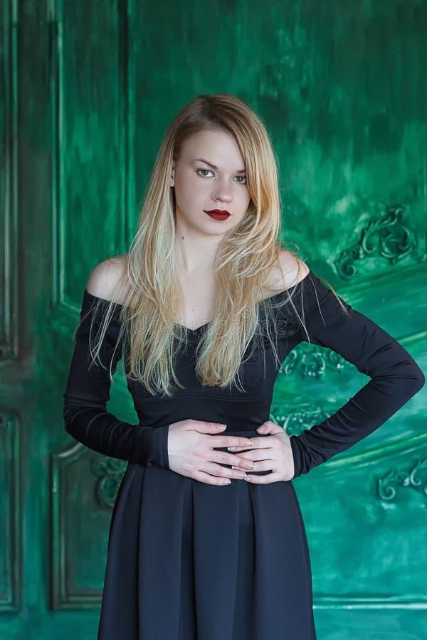 Elegant blonde in een zwarte kledings dichtbij grunge muur stock afbeelding