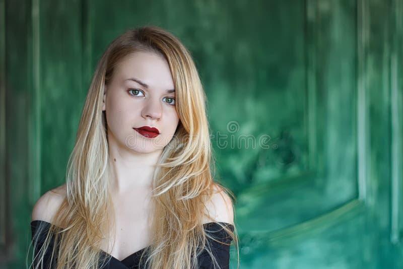 Elegant blonde in een zwarte kledings dichtbij grunge muur stock afbeeldingen