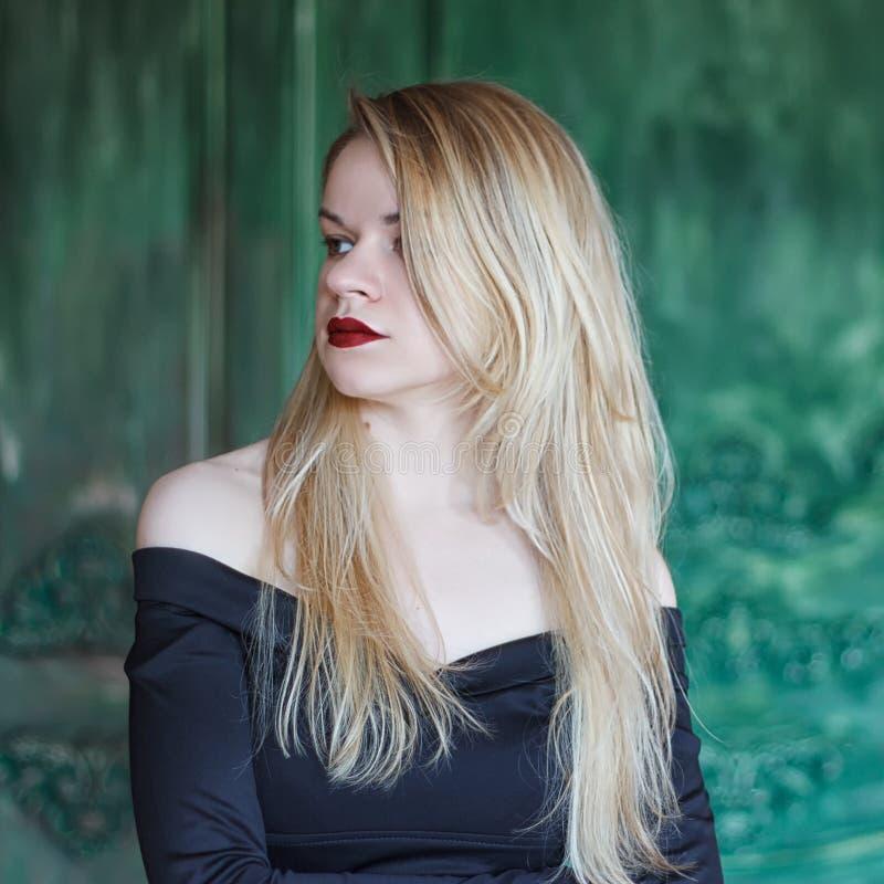 Elegant blonde in een zwarte kledings dichtbij grunge muur stock fotografie
