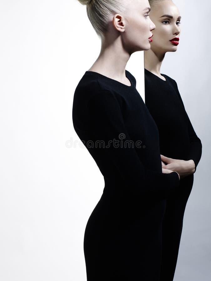 Elegant blonde en haar gedachtengang in de spiegel stock foto