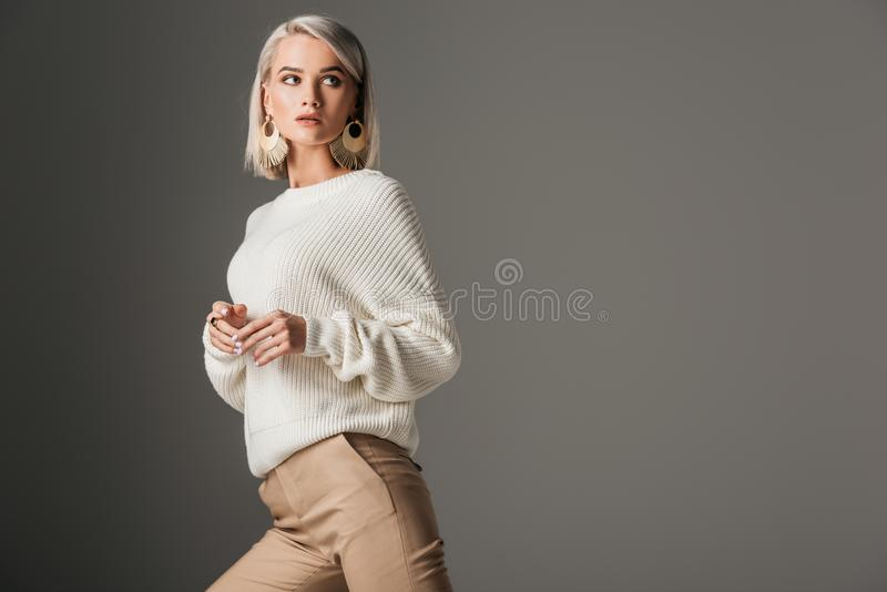Elegant blonde model posing in white knitted sweater. Isolated on grey royalty free stock images