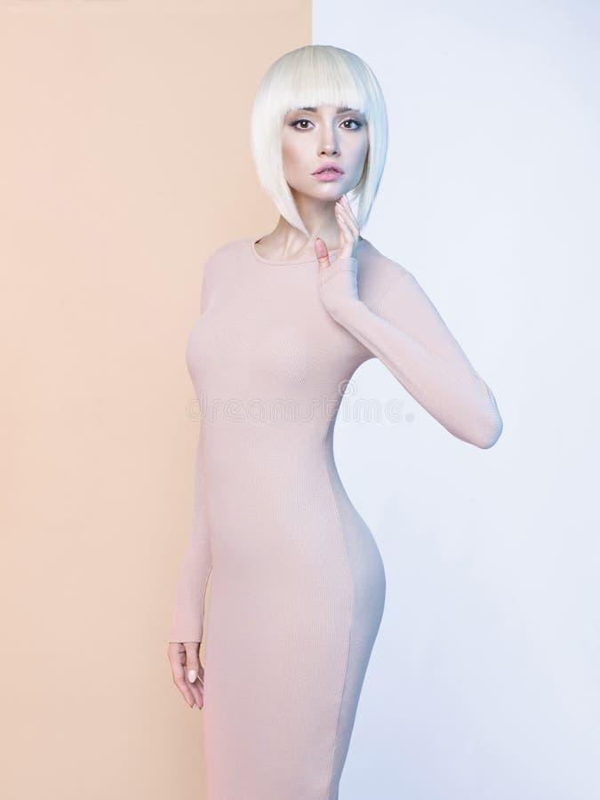 Elegant blonde op geometrische beige en witte achtergrond stock afbeelding