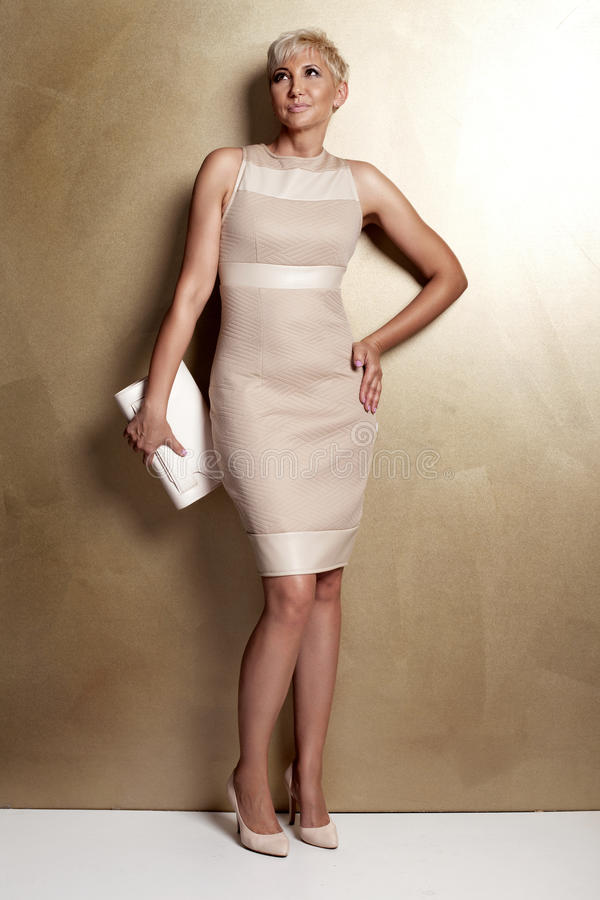Elegant blonde woman in fashionable dress. stock image