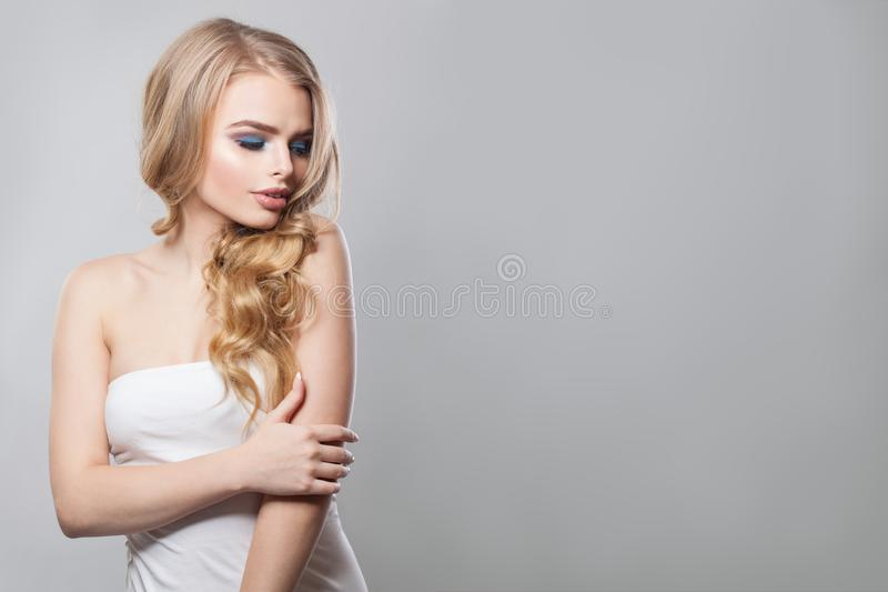 Elegant blonde woman with long healthy curly hair. Gorgeous woman with makeup and perfect hairstyle royalty free stock photography