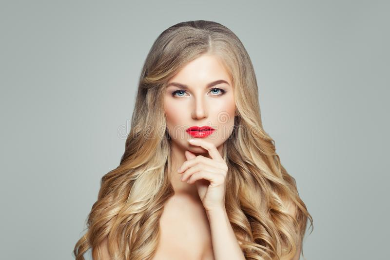 Elegant blonde woman with long wavy hair. Thinking fashion model portrait royalty free stock images