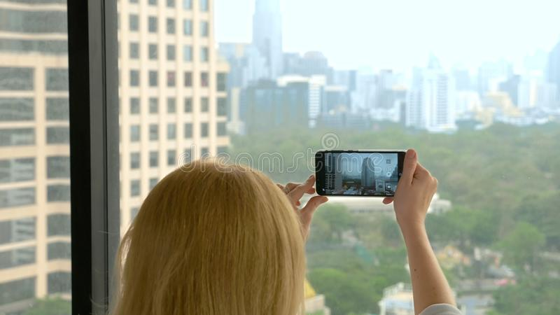 Elegant blonde woman making a photo on the phone. woman photographs the view from the window of the skyscrapers royalty free stock photography