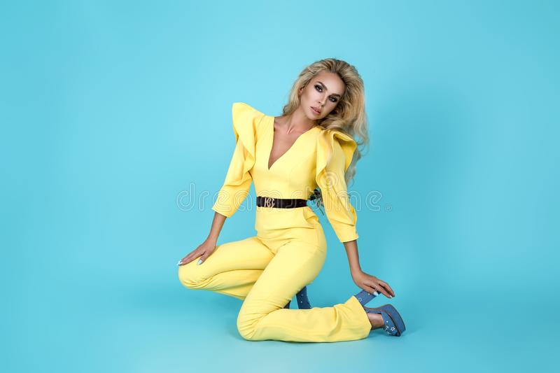 Elegant blonde woman in stylish yellow jumpsuit and fashionable accessories on color background. Beautiful fashion model on blue stock photo