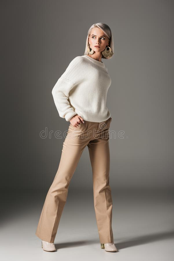 Elegant blonde woman posing in white sweater and beige pants. On grey royalty free stock photo