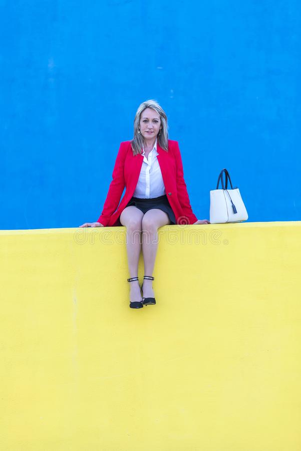 Free Elegant Blonde Woman Sitting On A Yellow Bench Relaxing Royalty Free Stock Photos - 130868378