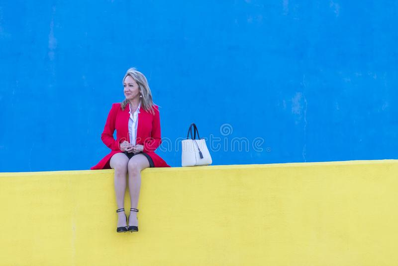 Elegant blonde woman sitting on a yellow bench relaxing stock photo