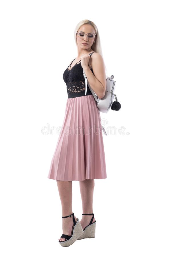 Elegant blonde woman wearing glasses carrying silver rucksack bag looking down. Side view. stock photo