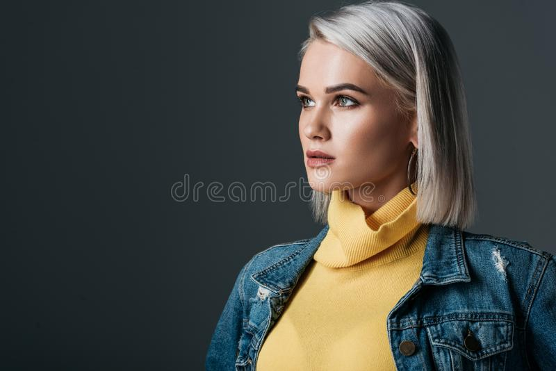 Elegant blonde woman in yellow turtleneck and jeans jacket. Isolated on grey royalty free stock photos