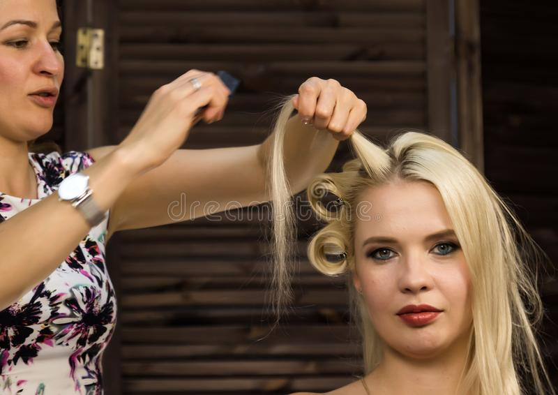 Elegant blonde woman in beauty saloon. Hairdresser does coiffure in the form of big curl. Concept wedding hairstyle royalty free stock photos