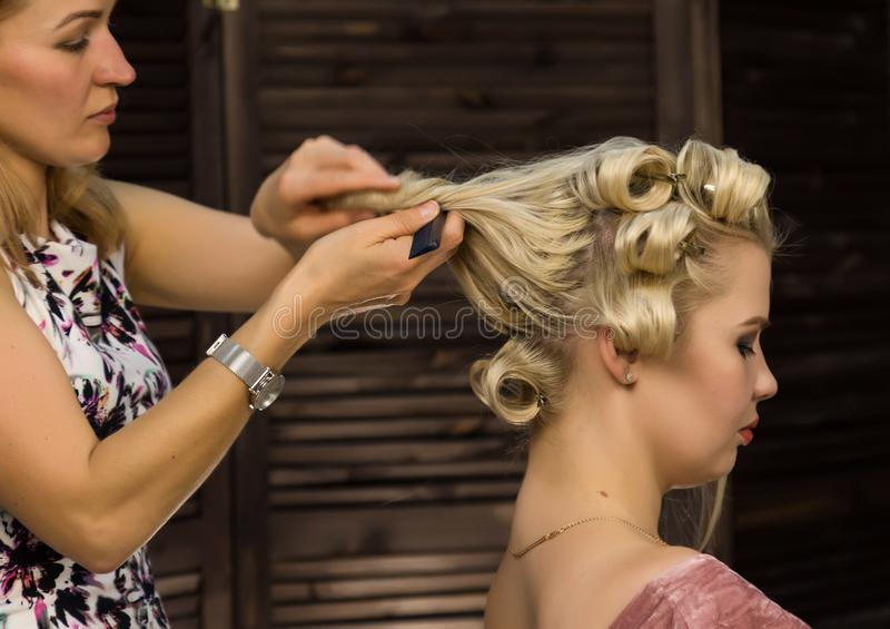 Elegant blonde woman in beauty saloon. Hairdresser does coiffure in the form of big curl. Concept wedding hairstyle. Elegant blonde women in beauty saloon stock image