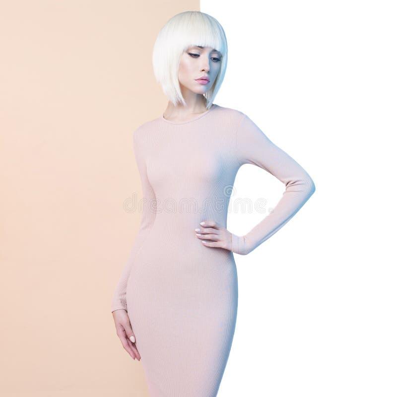 Elegant blondin i geometrisk beiga- och vitbakgrund fotografering för bildbyråer