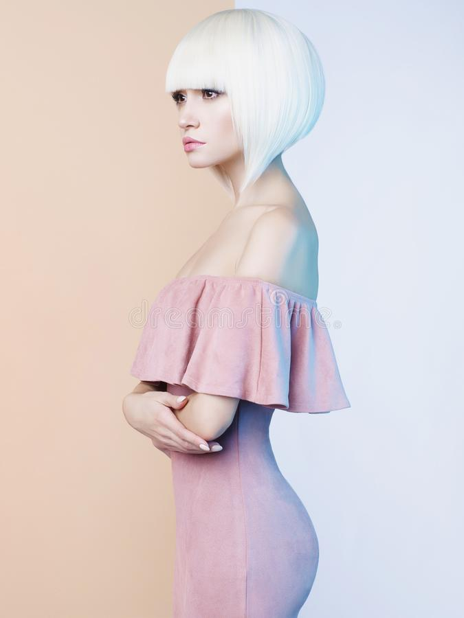 Elegant blondin i geometrisk beiga- och vitbakgrund arkivfoton