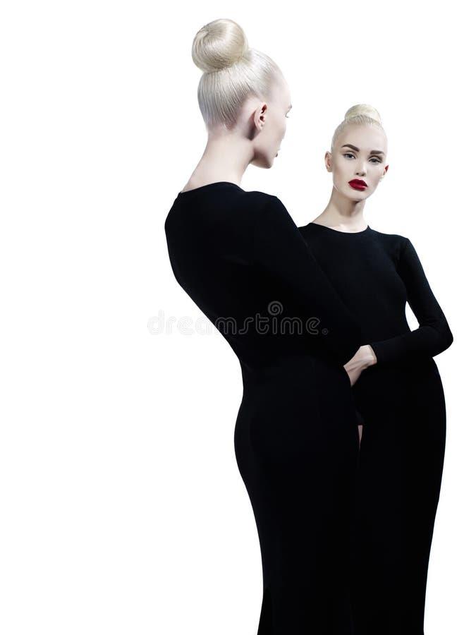 Elegant blondin och hennes reflexion i spegeln fotografering för bildbyråer