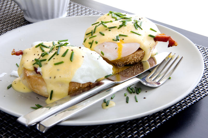 Elegant breakfast consists of eggs Benedict. On a toasted bun with bacon and delicious hollandaise sauce royalty free stock image