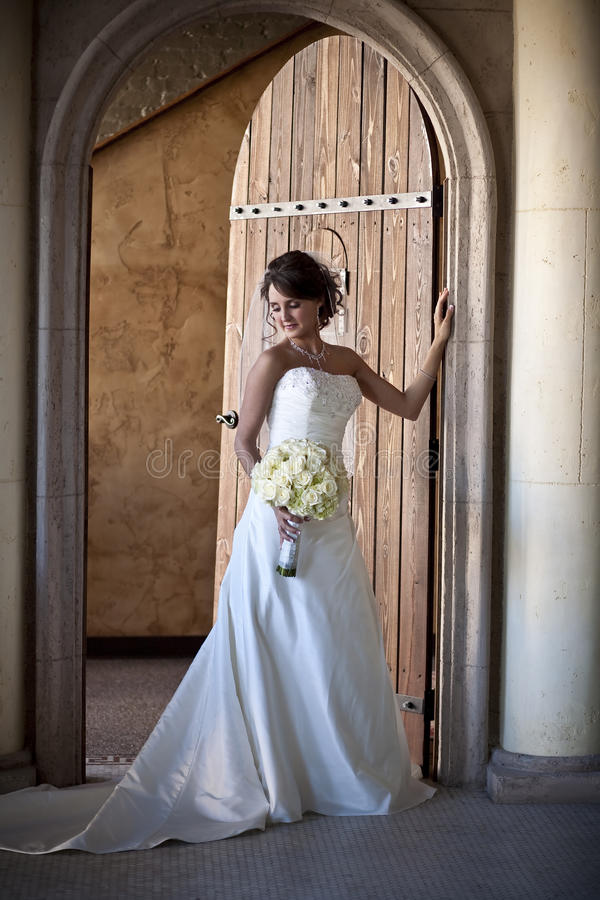 Elegant Bride. Vertical image of a beautiful bride in a doorway stock image