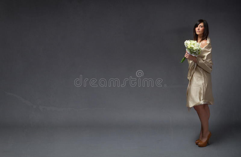 Elegant bride with bouquet on hand. Dark background royalty free stock images