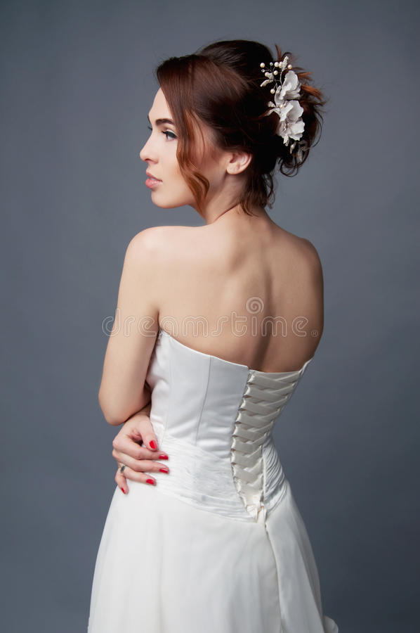 Elegant bride with short hair updo and bare shoulders dress. Elegant bride with brown short hair updo and bare shoulders white wedding dress stock image