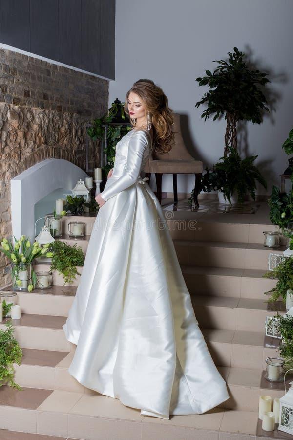 Elegant brud för härlig söt flicka i en elegant bröllopplatestoit på trappan arkivfoton