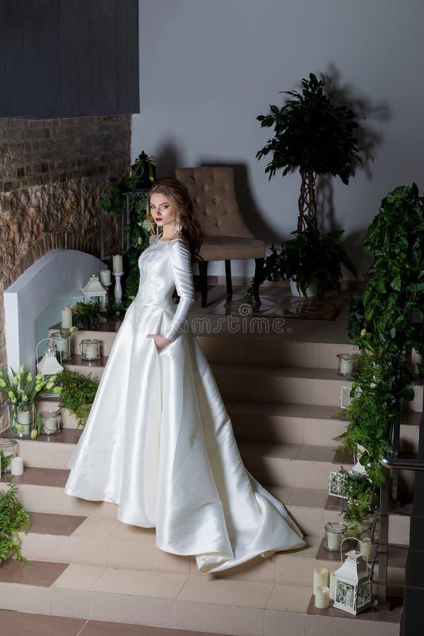 Elegant brud för härlig söt flicka i en elegant bröllopplatestoit på trappan arkivbilder
